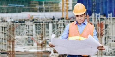 Engenheiro civil analisando a planta de um edifício - Construção Civil 2020