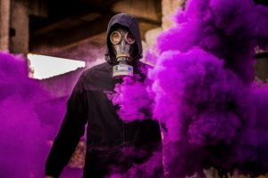 man wearing mask with purple smoke background