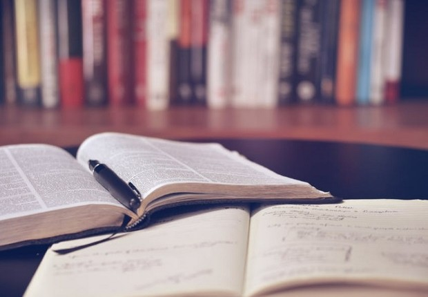Imagem de livro e caderno abertos sobre mesa, com livros em segundo plano em estante